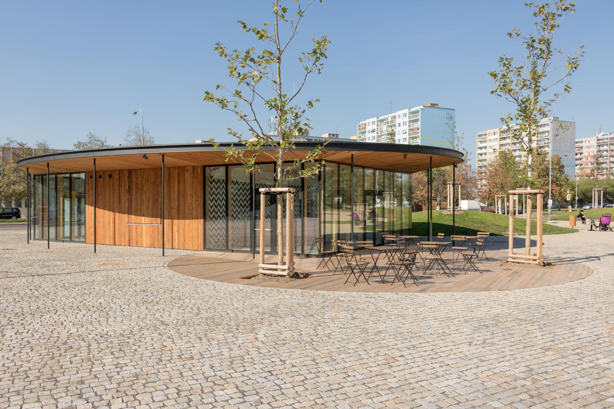 Eliptická střecha pavilonu přesahuje jeho obdélníkový půdorys a vytváří potřebné zastínění a ochranu před deštěm.